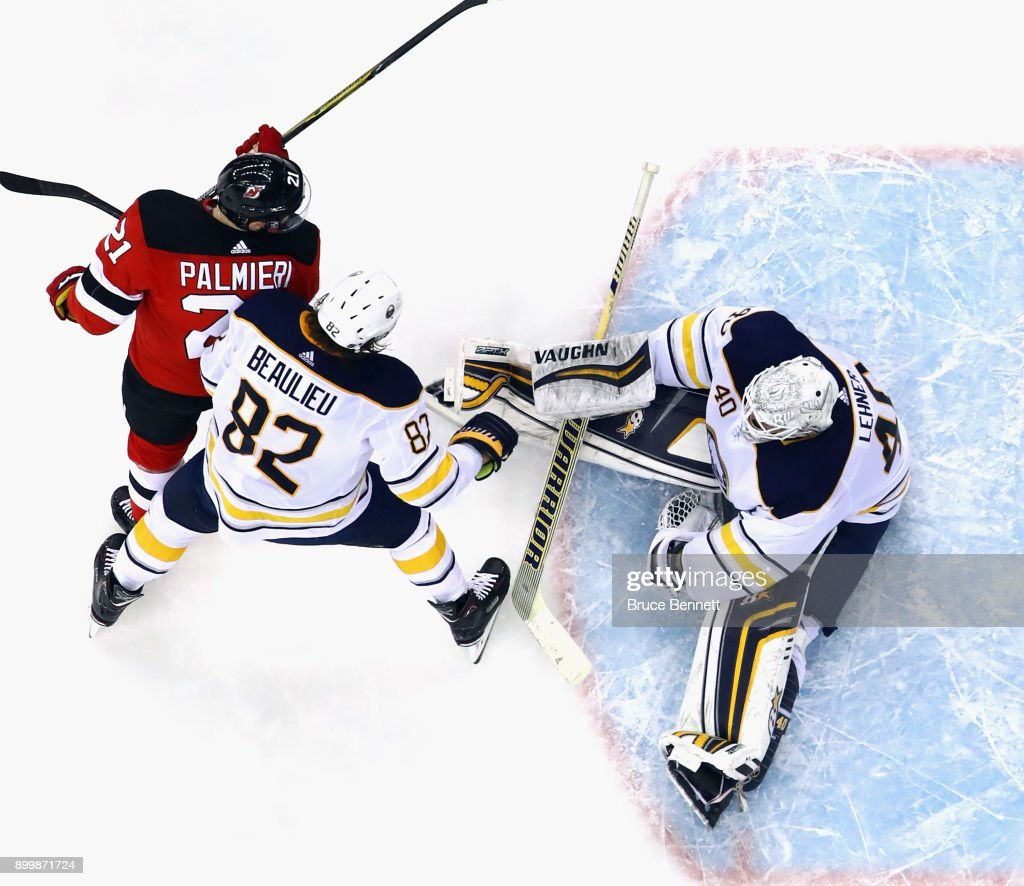 Robin Lehner #40 of the Buffalo Sabres makes the save as Kyle Palmieri #21 of the New Jersey Devils looks for the rebound at the Prudential Center on December 29, 2017 in Newark, New Jersey. The Sabres defeated the Devils 4-3 in overtime.