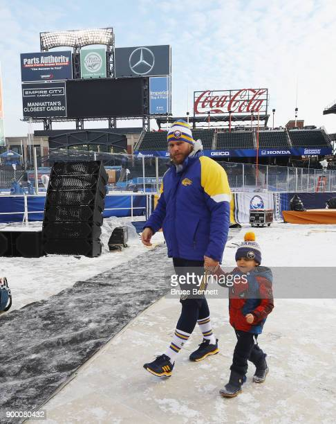 Robin Lehner of the Buffalo Sabres walks the field with his son prior to practice at Citi Field on December 31 2017 in the Flushing neighborhood of...