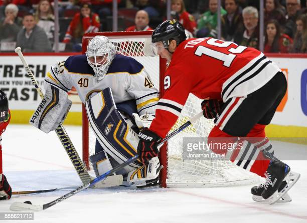 Robin Lehner of the Buffalo Sabres watches as Jonathan Toews of the Chicago Blackhawks readies to shoot at the United Center on December 8 2017 in...