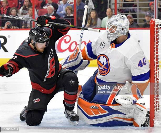 Robin Lehner of the New York Islanders fends off Warren Foegele of the Carolina Hurricanes in the crease during the second period of Game Three of...
