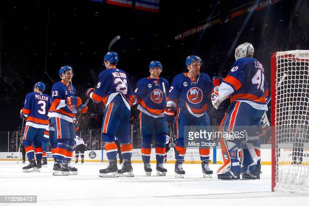 Robin Lehner of the New York Islanders is congratulated by his teammates after his 20 shutout win against the Arizona Coyotes at NYCB Live's Nassau...