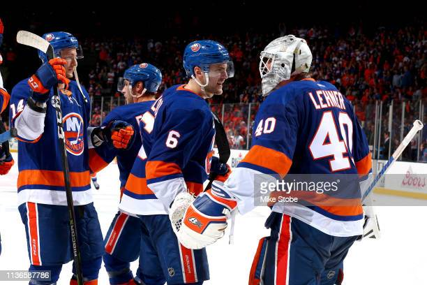 Robin Lehner of the New York Islanders is congratulated by his teammates Tom Kuhnhackl and Ryan Pulock after their teams 31 win over the Pittsburgh...