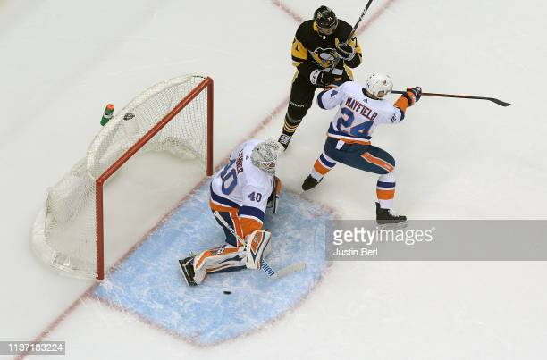Robin Lehner of the New York Islanders makes a save as Scott Mayfield battles in front with Evgeni Malkin of the Pittsburgh Penguins during the first...