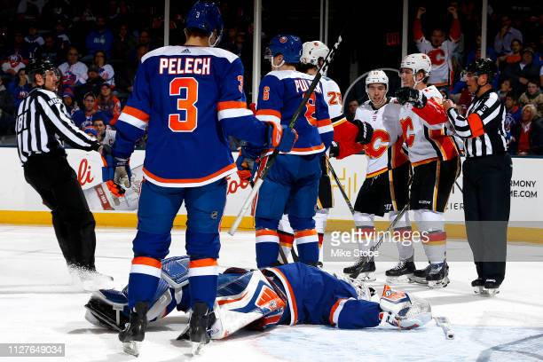 Robin Lehner of the New York Islanders reacts after allowing a second period goal to Matthew Tkachuk of the Calgary Flames who is congratulated by...