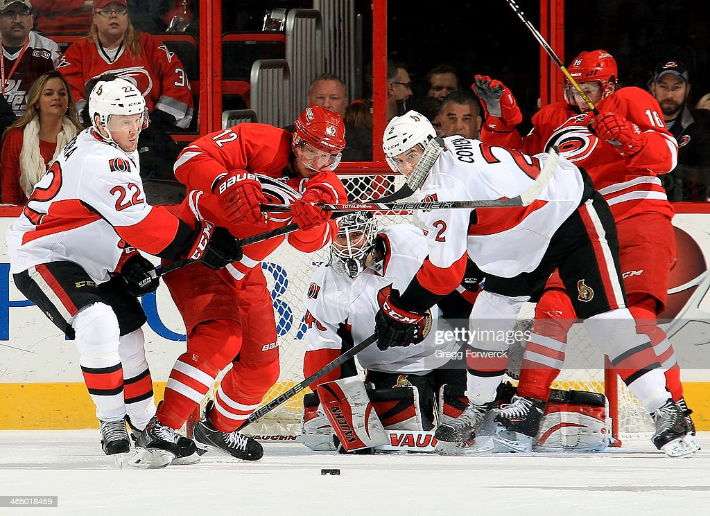 Robin Lehner #40 of the Ottawa Senators eyes the puck through traffic created by Eric Staal #12 and Elias Lindholm #16 of the Carolina Hurricanes who are defended by Senators Erik Condra #22 and Jared Cowen #2 during their NHL game at PNC Arena on January 25, 2014 in Raleigh, North Carolina.