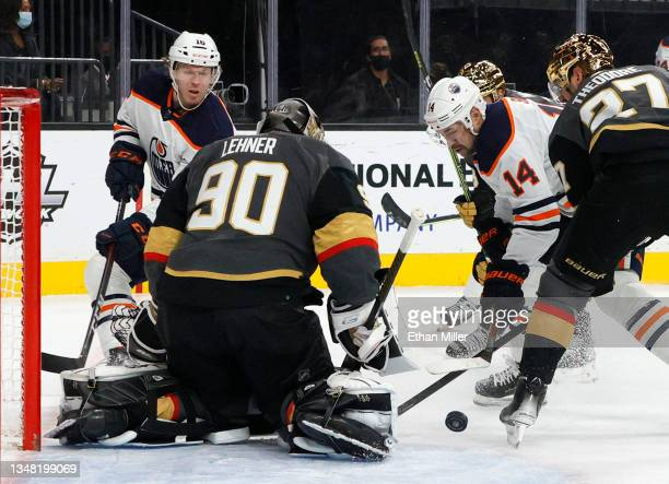 Robin Lehner of the Vegas Golden Knights defends the net against Tyler Benson and Devin Shore of the Edmonton Oilers in the first period of their...