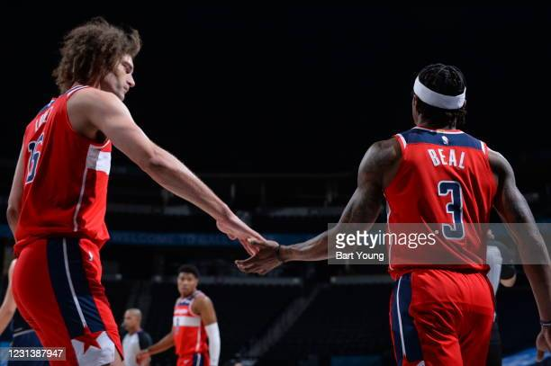 Robin Lopez and Bradley Beal of the Washington Wizards hi-five during the game against the Denver Nuggets on February 25, 2021 at the Ball Arena in...