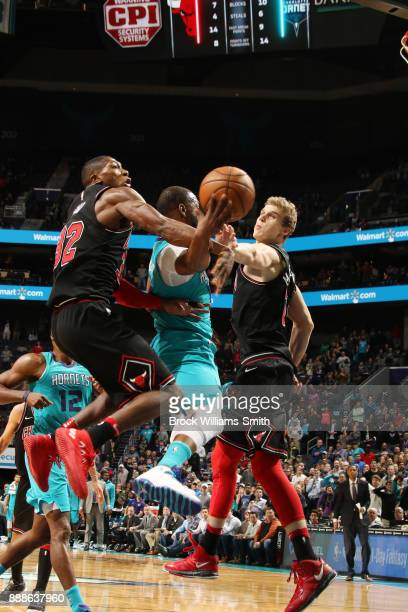 Robin Lopez and Lauri Markkanen of the Chicago Bulls block the shot against Kemba Walker of the Charlotte Hornets on December 8 2017 at Spectrum...