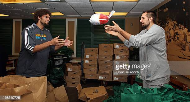 Robin Lopez and Ryan Anderson of the New Orleans Hornets distribute Thanksgiving baskets provided by the Hornets and Rouses to Emerge students on...