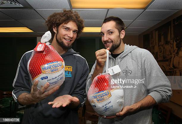 Robin Lopez and Ryan Anderson of the New Orleans Hornets pose for a photo during the distribution of Thanksgiving baskets provided by the Hornets and...