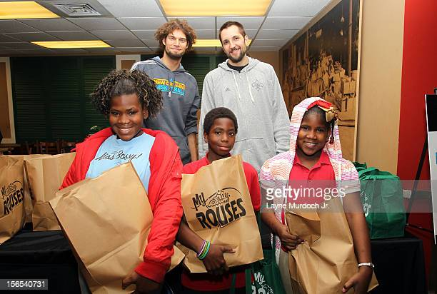 Robin Lopez and Ryan Anderson of the New Orleans Hornets pose with kids during the distribution of Thanksgiving baskets provided by the Hornets and...
