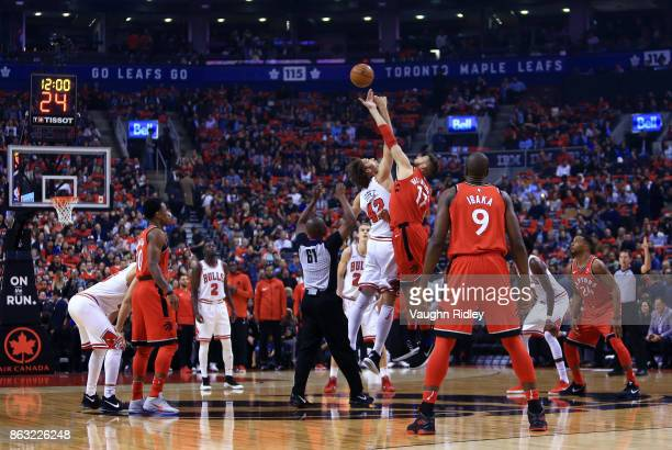 Robin Lopez of the Chicago Bulls contests the opening tip off with Jonas Valanciunas of the Toronto Raptors during the first half of an NBA game at...