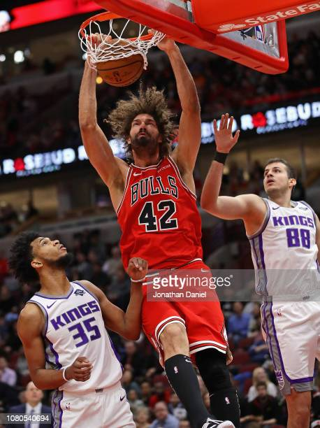 Robin Lopez of the Chicago Bulls dunks between Marvin Bagley III and Nemanja Bjelica of the Sacramento Kings at the United Center on December 10,...