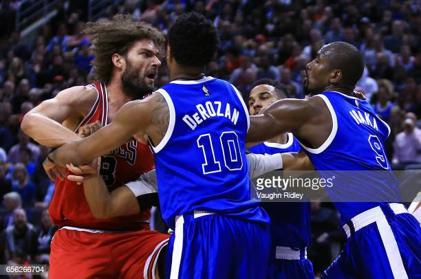 Robin Lopez of the Chicago Bulls fights with DeMar DeRozan and Serge Ibaka of the Toronto Raptors during the second half of an NBA game at Air Canada...