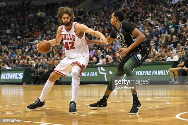 Robin Lopez of the Chicago Bulls is defended by John Henson of the Milwaukee Bucks during a game at the Bradley Center on December 15 2017 in...