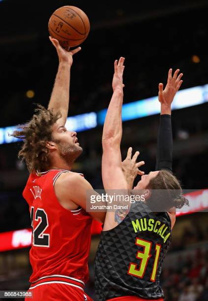 Robin Lopez of the Chicago Bulls puts up a shot over Mike Muscala of the Atlanta Hawks at the United Center on October 26 2017 in Chicago Illinois...