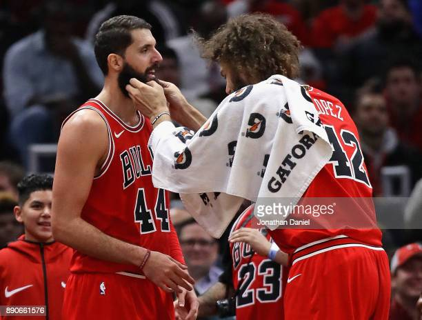 Robin Lopez of the Chicago Bulls tickles the beard of Nikola Mirotic of the Chicago Bulls after Mirotic came out of the game against the Boston...