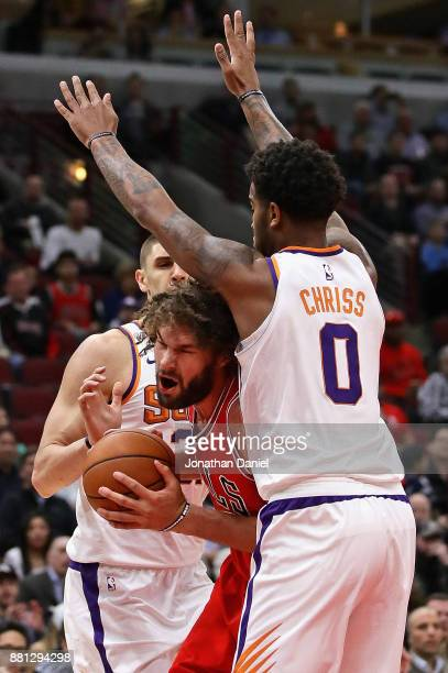 Robin Lopez of the Chicago Bulls tries to move between Alex Len and Marquese Chriss of the Phoenix Suns at the United Center on November 28 2017 in...