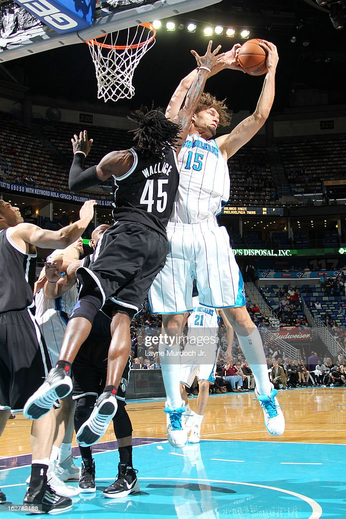 Robin Lopez #15 of the New Orleans Hornets rebounds against Gerald Wallace #45 of the Brooklyn Nets on February 26, 2013 at the New Orleans Arena in New Orleans, Louisiana.