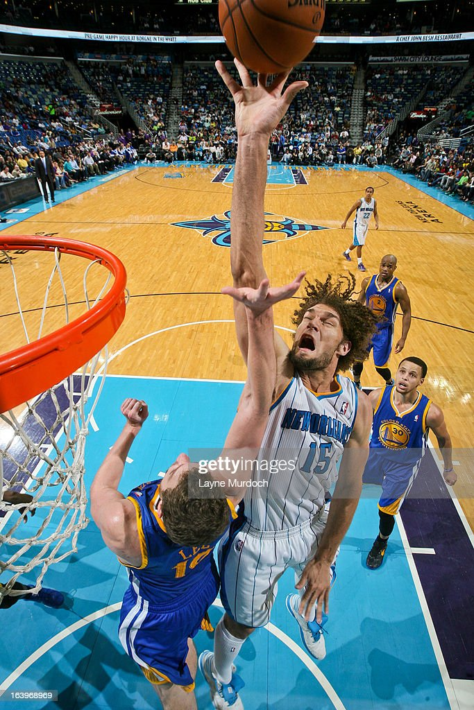 Robin Lopez #15 of the New Orleans Hornets shoots in the lane against David Lee #10 of the Golden State Warriors on March 18, 2013 at the New Orleans Arena in New Orleans, Louisiana.