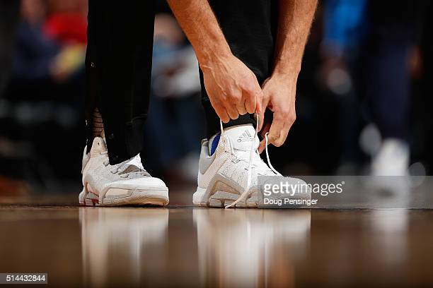 Robin Lopez of the New York Knicks ties his shoes as he prepares to face the Denver Nuggets at Pepsi Center on March 8 2016 in Denver Colorado The...