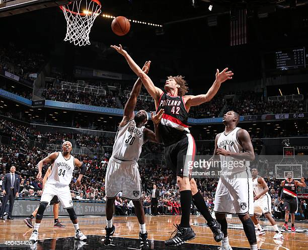 Robin Lopez of the Portland Trail Blazers shoots against Reggie Evans of the Brooklyn Nets during a game at Barclays Center on November 18 2013 in...