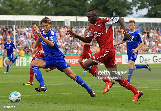 Robin Menzel of Jena and Jacques Daogari Zoua of Hamburg battle for the ball during the DFB Cup between SV Schott Jena and Hamburger SV at...