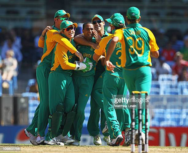 Robin Peterson of South Africa is congratulated by team mates after he caught and bowled Ian Bell of England during the 2011 ICC World Cup match...