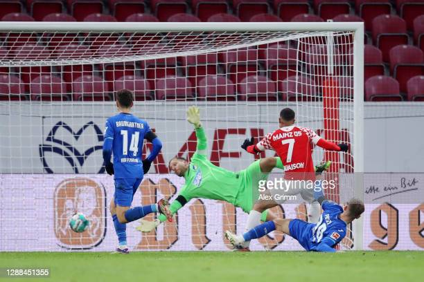 Robin Quaison of 1. FSV Mainz 05 scores their sides first goal past Oliver Baumann of TSG 1899 Hoffenheim whilst under pressure from Stefan Posch of...