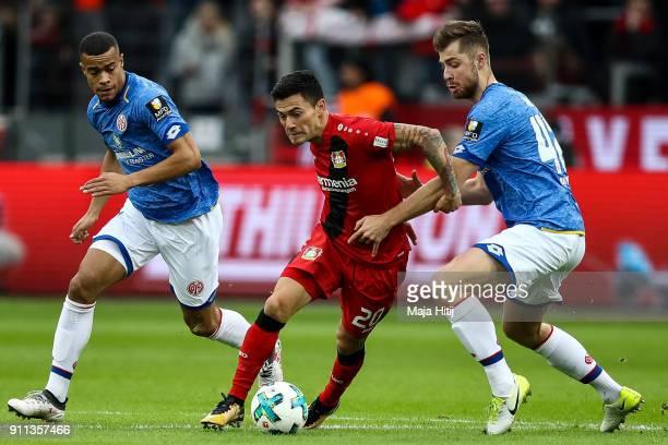 Robin Quaison of FSV Mainz 05 Charles Aranguiz of Bayer Leverkusen and Alexander Hack of FSV Mainz 05 battle for the ball during the Bundesliga match...