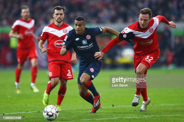 Robin Quaison of FSV Mainz battles for the ball with Robin Bormuth and Kevin Stoger of Fortuna Dusseldorf during the Bundesliga match between Fortuna...