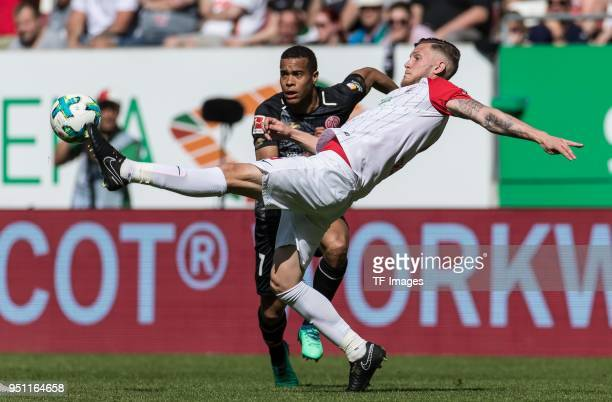 Robin Quaison of Mainz and Jeffrey Gouweleeuw of Augsburg battle for the ball during the Bundesliga match between FC Augsburg and 1 FSV Mainz 05 at...