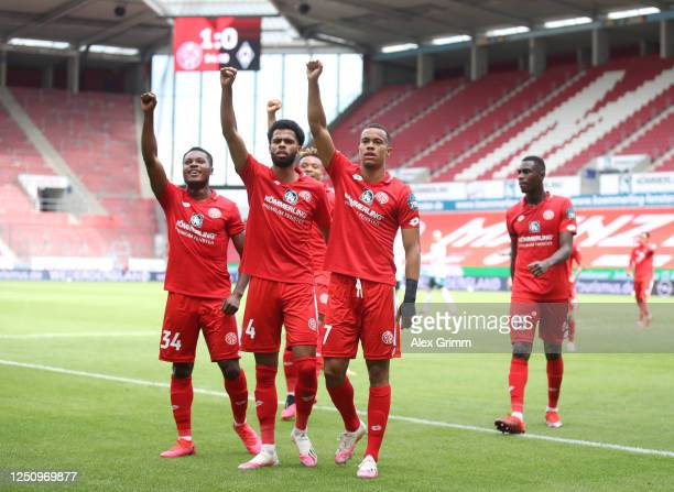 Robin Quaison of Mainz celebrates scoring his team's first goal as his raises his hand in salute with Jeremiah St. Juste and Bote Baku during the...