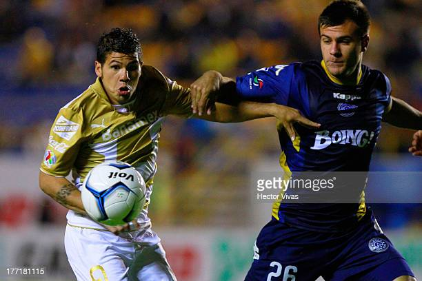 Robin Ramirez of Pumas fights for the ball with Alfonso Rippa of San Luis during a match between San Luis and Pumas as part of the Apertura 2013 Copa...