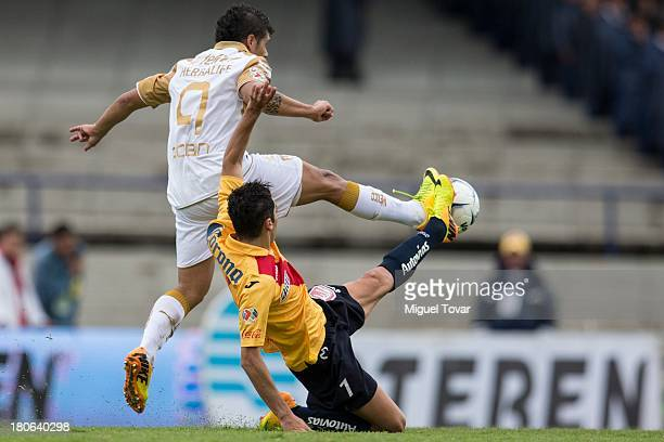 Robin Ramirez of Pumas fights for the ball with Jose Cardenas of Morelia during a match between Pumas and Morelia as part of the Apertura 2013 Liga...