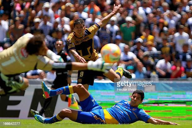Robin Ramirez of Pumas struggles for the ball with Hugo Ayala of Tigres during a match between Pumas and Tigres as part of the Clausura 2013 Liga MX...