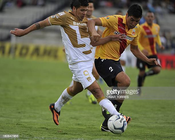 Robin Ramirez of Pumas vies for the ball in with Enrique Perez of Morelia during their Mexican Apertura tournament football match on September 15...