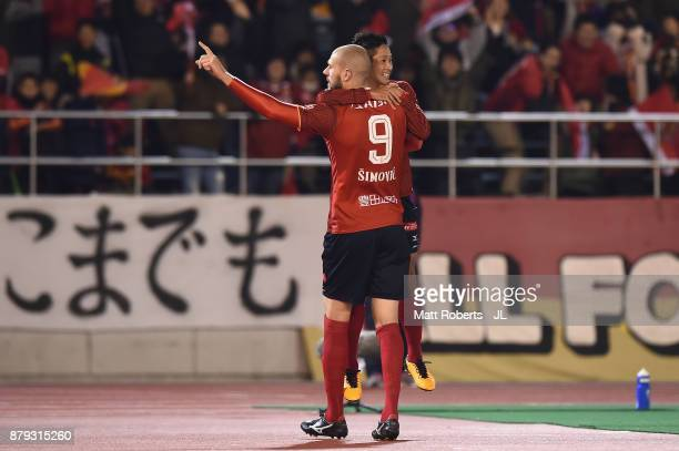 Robin Simovic of Nagoya Grampus celebrates scoring his side's third goal with his team mate Ryota Aoki during the JLeague J1 Promotion PlayOff semi...
