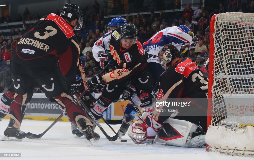 Robin Thomson (C) of Hannover and Craig MacDonald (#10) of Mannheim battle for the puck in front of the net during the DEL match between Hannover Scorpions and Aadler Mannheim at TUI Arena on October 14, 2012 in Hanover, Germany.