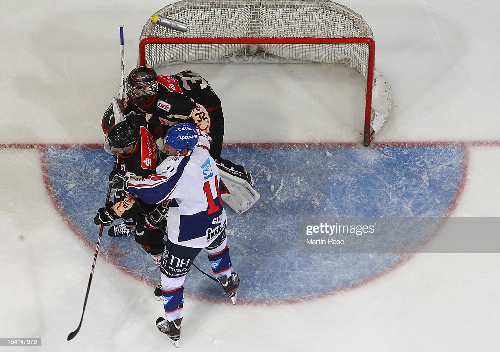 Robin Thomson (L) of Hannover and Michael Glumac (R) of Mannheim battle for position in front of the net during the DEL match between Hannover Scorpions and Aadler Mannheim at TUI Arena on October 14, 2012 in Hanover, Germany.