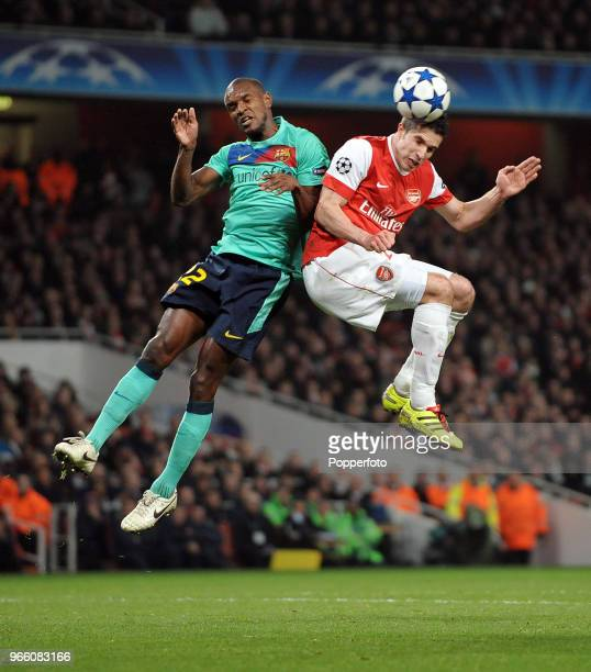 Robin van Persie of Arsenal and Eric Abidal of Barcelona both go for a high ball during the UEFA Champions League round of 16 first leg match between...