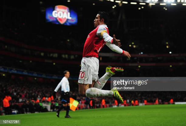 Robin van Persie of Arsenal celebrateds as he scores their first goal from the penalty spot during the UEFA Champions League Group H match between...