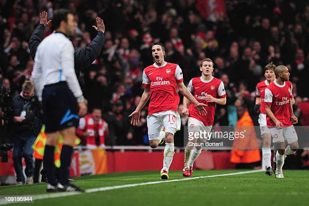 Robin van Persie of Arsenal celebrates Arsenal's first goal during the UEFA Champions League round of 16 first leg match between Arsenal and...