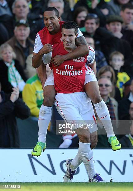 Robin van Persie of Arsenal celebrates his second goal with teammate Theo Walcott during the Barclays Premier League match between Norwich City and...