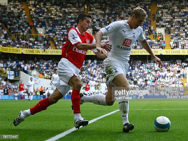 Robin Van Persie of Arsenal challenges Michael Dawson of Tottenham during the Barclays Premier League match between Tottenham Hotspur and Arsenal at...