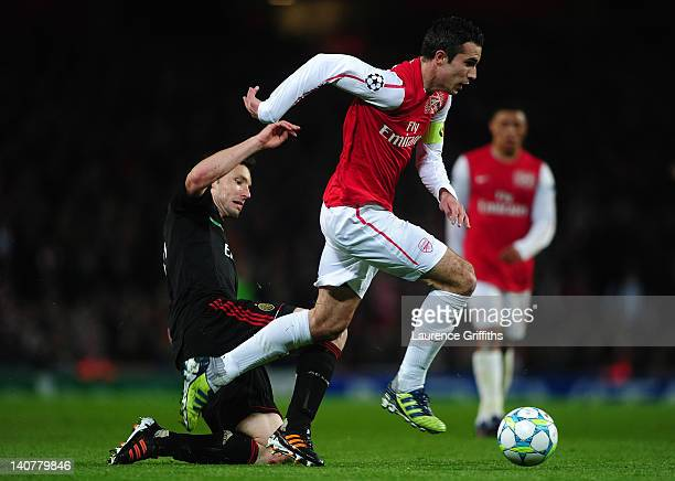 Robin van Persie of Arsenal is tackled by Mark van Bommel of AC Milan during the UEFA Champions League Round of 16 second leg match between Arsenal...