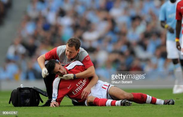 Robin van Persie of Arsenal receives treatment after a challenge from Emmanuel Adebayor of Manchester City during the Barclays Premier League match...