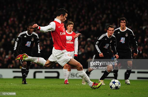 Robin van Persie of Arsenal scores their first goal from the penalty spot during the UEFA Champions League Group H match between Arsenal and FK...