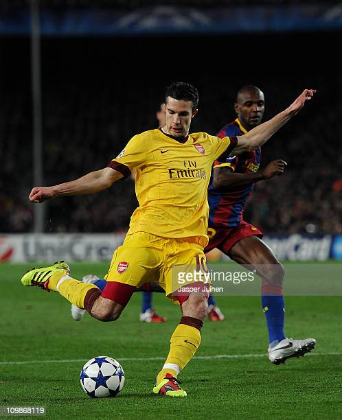 Robin van Persie of Arsenal shoots on goal from offside position past Eric Abidal of Barcelona during the UEFA Champions League round of 16 second...