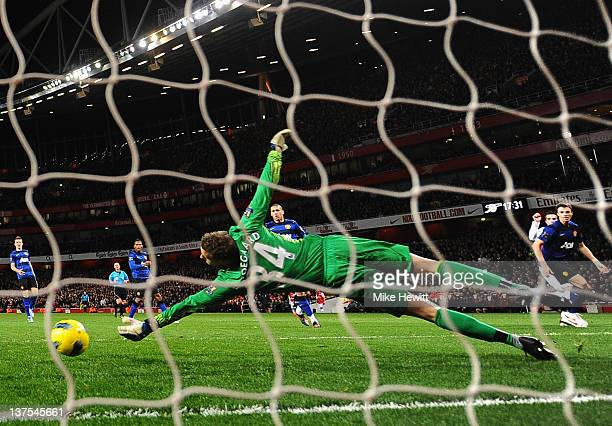 Robin van Persie of Arsenal shoots past Anders Lindegaard of Manchester United to score their first goal during the Barclays Premier League match...